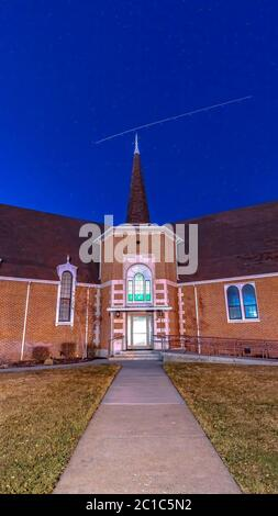 Vertical frame Front view of a beautiful brick church in Provo Utah with deep blue sky overhead