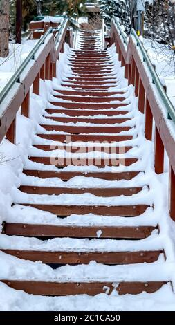 Vertical Focus on stairway that goes up a snowy hill with residential homes in winter - Stock Photo