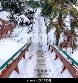 Square frame Grate metal tread stairway on hill slope blanketed with snow during winter - Stock Photo