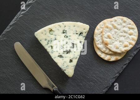 Rochefort cheese and crackers close up top view on black slate board - Stock Photo