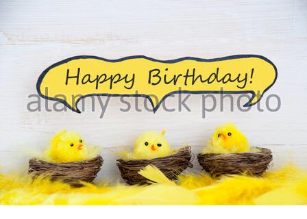 Three Sitting Easter Chicks In Easter Baskets Or Nest With Yellow Feathers On White Wooden Background With Comic Speech Balloon With English Text Happ - Stock Photo