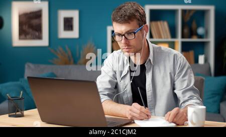 Man looking laptop making notes