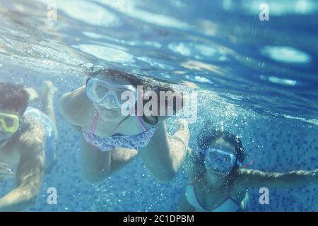 Little girl and friends having fun in pool - Stock Photo