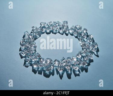Round frame of pure ice cubes on a blue background - Stock Photo