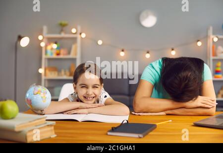 Stress work with children at home office. Tired mother sleeping on a desktop naughty daughter smiling looking at camera at home office.