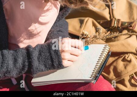 Stylish girl designer painter in the mountains sitting on a rock draws in a notepad at sunset - Stock Photo