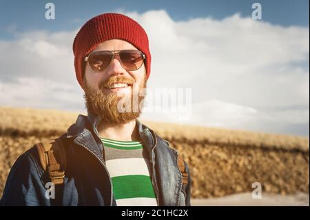 Portrait of a young hipster man wearing sunglasses and a hat. A smiling bearded man wearing sunglasses. Happy man with a beard - Stock Photo