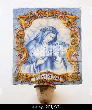 Portugal Typical old Portuguese 'azulejos' - blue and white ceramic tiles depicting Saint Stephanie - Santa Estefania, with Christ on the cross. - Stock Photo