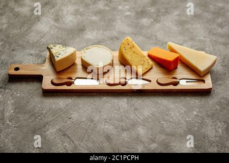 Assortment of various kinds of cheeses served on wooden board with fork and knives - Stock Photo