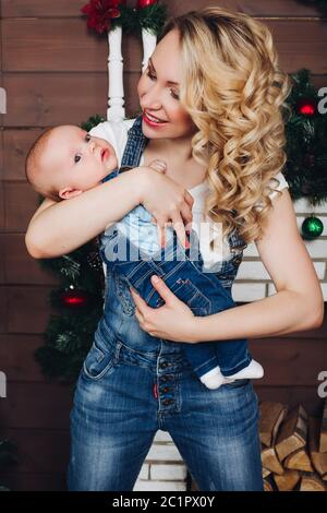 Boy with beautiful blonde mom embracing in decorated studio for Christmas.