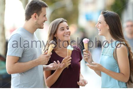 Three happy friends talking and eating ice creams in the street - Stock Photo