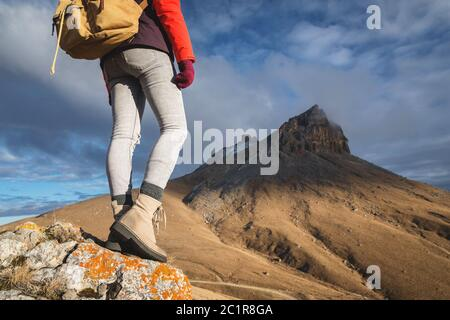 Close-up from the back of a girl traveler on the background of the epic rocks outdor. Portrait below the belt - Stock Photo