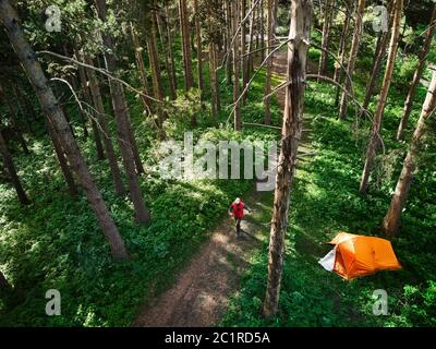 Aerial view of man walking near orange tent at forest in the mountains. Photo taken with Drone