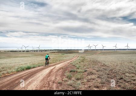 Man on mountain bike rides on the road to the wind turbines farm near the lake Against blue cloudy sky. Ecological and zero waste lifestyle concepts.