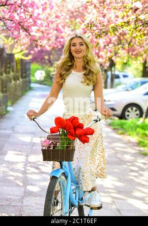 Travel concept. Bike ride tours. Summer vacation. Riding bicycle. Girl and sakura blossom. Cycling Tours. Bike ride adventure. Urban excursion. Cherry tree blooming. Woman ride retro bicycle. - Stock Photo
