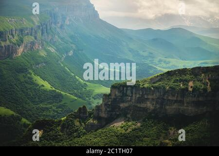 Dramatic landscape of a green valley at the foot of the Inal Plateau in the North Caucasus - Stock Photo