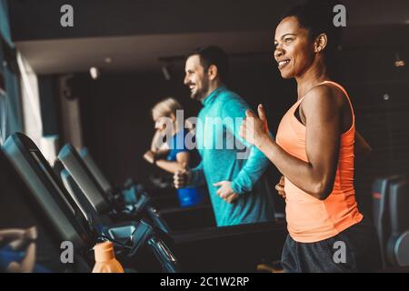 Young people running on a treadmill in modern gym