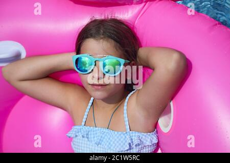 Portrait of little girl wearing sunglasses on inflatable flamingo swim float - Stock Photo