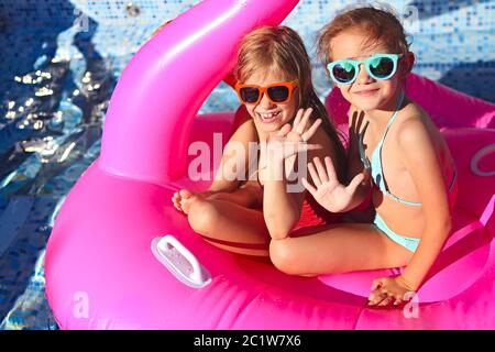 Portrait of two girls wearing sunglasses, happy friends on inflatable flamingo swim float - Stock Photo