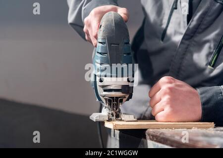 Close up of carpenter's hands working power tools for processing wood. Power Jigsaw