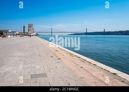 View facing east towards the Monument to the Discoveries and the 25 April Bridge, on the River Tagus promenade at Belém, Lisbon, Portugal. - Stock Photo
