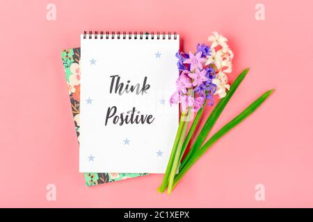 White notebook for notes, bouquet of hyacinths flowers on pink background Flat lay Top view Text Think Positive - motivational slogan Creative concept - Stock Photo