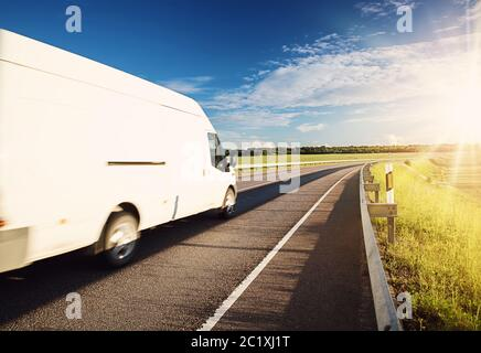 asphalt road on dandelion field with a small truck - Stock Photo
