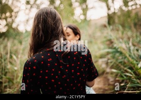 Back view of two young women walking through the field - Stock Photo