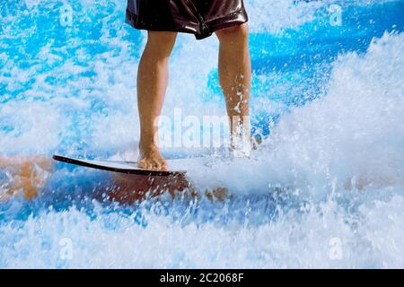 Man take wake surf, riding a surfboard or foot board along an outdoor water slide set up - Stock Photo