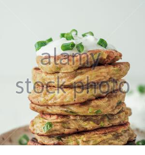 Zucchini fritters. Gluten free zucchini fritters in stack on white background. Vegetable zucchini pancakes or fritters with green onion and parmesan c - Stock Photo