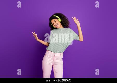 Portrait of trendy funky crazy afro american girl listen music using wireless headset sing song dance wear striped shirt pants pink trousers isolated