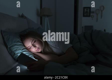 Young sleepy tired woman with half-closed tired eyes lying in bed under the blanket using smartphone at late night, can not sleep.Insomnia, nomophobia