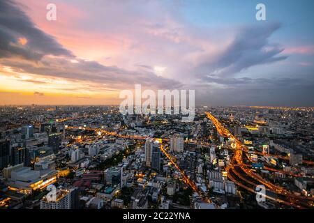 Bangkok: Bangkok / Thailand - July 18, 2019: aerial view of Bangkok, Thailand, from a sky bar in the city, at sunset, with lot of city lights and traf