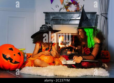 Two girls in Halloween costumes sit near burning fireplace - Stock Photo