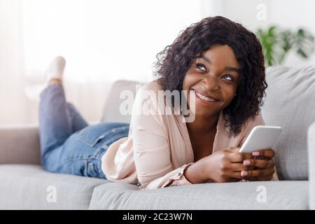 Dreamy black girl lying on couch and messaging on smartphone at home