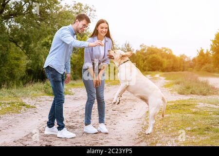 Young couple giving a treat to their happy dog