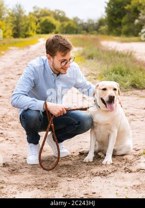 Excited man and his golden retriever sitting outside