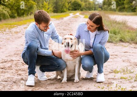 Portrait of happy young couple hugging their lovely dog
