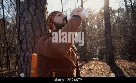 A young tired Caucasian man carries a rest break with a backpack sitting and drinking water on a tree in a nature forest during