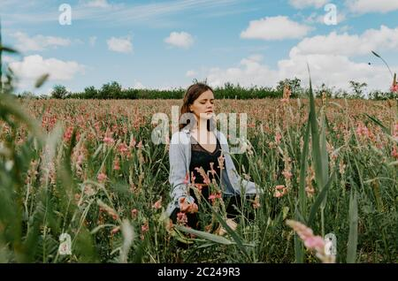 Young woman sitting cross legged in meditation in a flower field in blossom front view