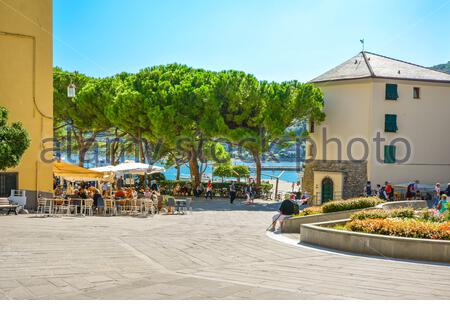 A sunny day on the Ligurian Coast as tourists enjoy cafes and relaxation on the  Piazza Bastreri in the coastal village of Portovenere, Italy - Stock Photo