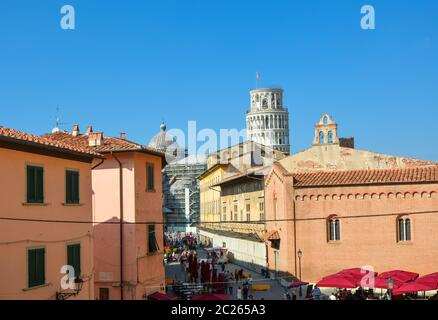 Tourists enjoy afternoon sightseeing on the Via Santa Maria, the busy tourist street leading to the Leaning tower of Pisa in the Tuscany area of Italy - Stock Photo