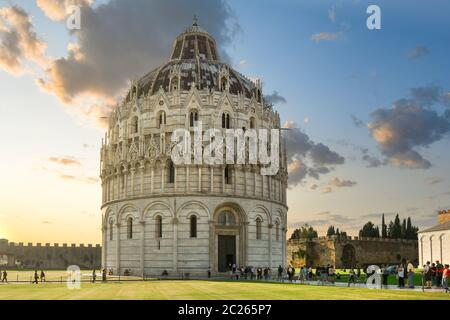 The historic, round Baptistery next to the tower and Duomo on the Field of Miracles, in the Tuscan city of Pisa Italy at sunset. - Stock Photo