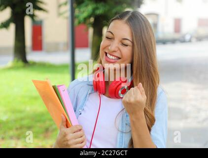 Portrait of excited laughing teenager girl with raising arm celebrating outdoors.