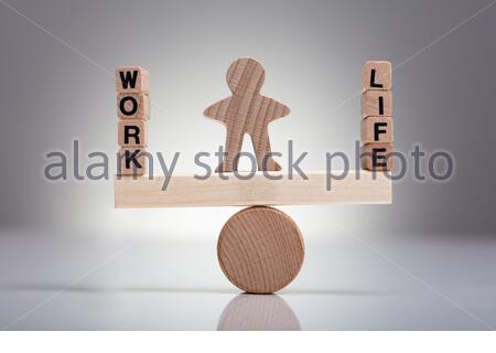 Human Figure Balancing Between Work And Life On Wooden Seesaw Against Gray Background - Stock Photo