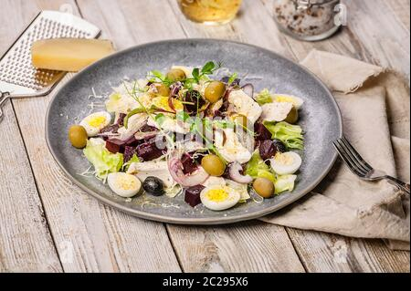 Close-up beets salad with ice lettuce, sweet onions, sheeps spicy cheese, olives, micro-greens and olive oil. Mediterranean diet. - Stock Photo
