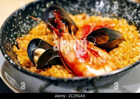 Paella with mariscos, a typical dish of traditional Spanish cuisine based on seafood and rice - Stock Photo
