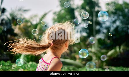 Back view of happy little girl playing soap bubbles on the nature