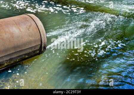 Water flows from the pipe into the river. - Stock Photo