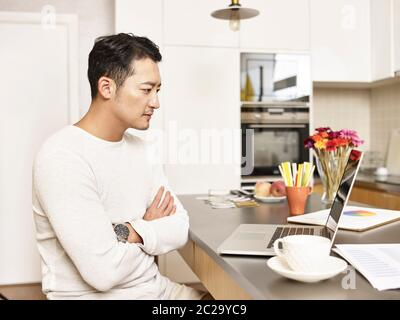 young asian businessman working from home sitting at kitchen counter looking at laptop computer arms crossed